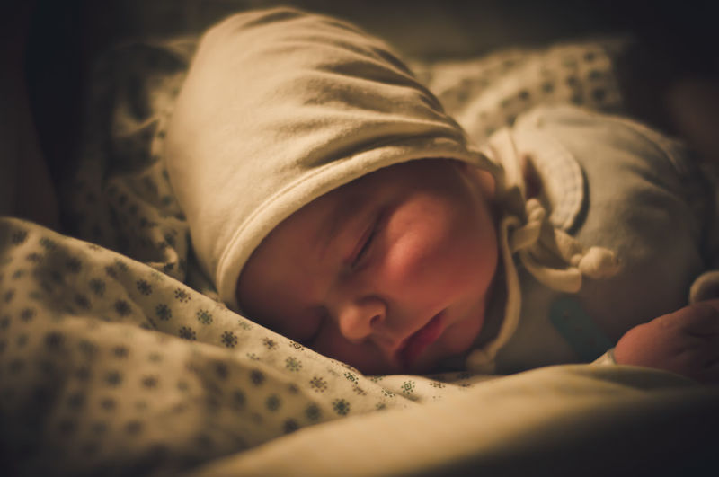 Cute baby boy sleeping on bed at home
