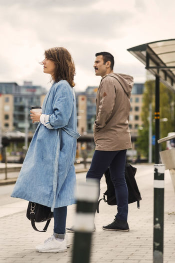 Man and woman walking with umbrella in city against sky