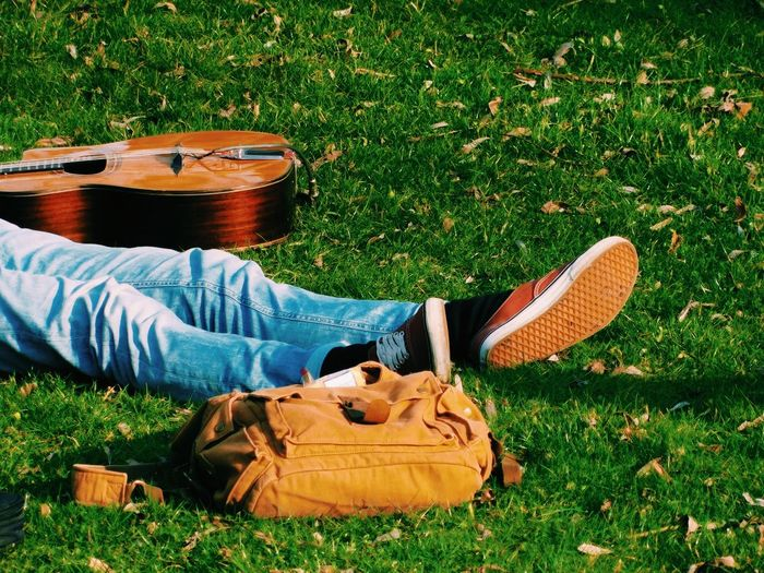 Low section of man by lying by guitar and bag at park