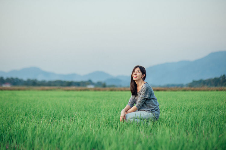 Smiling woman crouching on field against sky