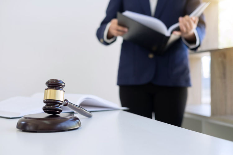 Midsection Of Judge Holding Book While Standing By Table