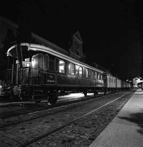 Train at railroad station against sky at night
