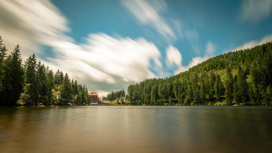 Lake With Trees And House Against Cloudy Sky