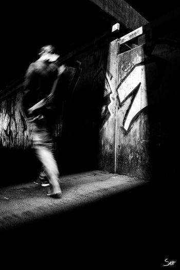 Blurred motion of man walking in illuminated corridor