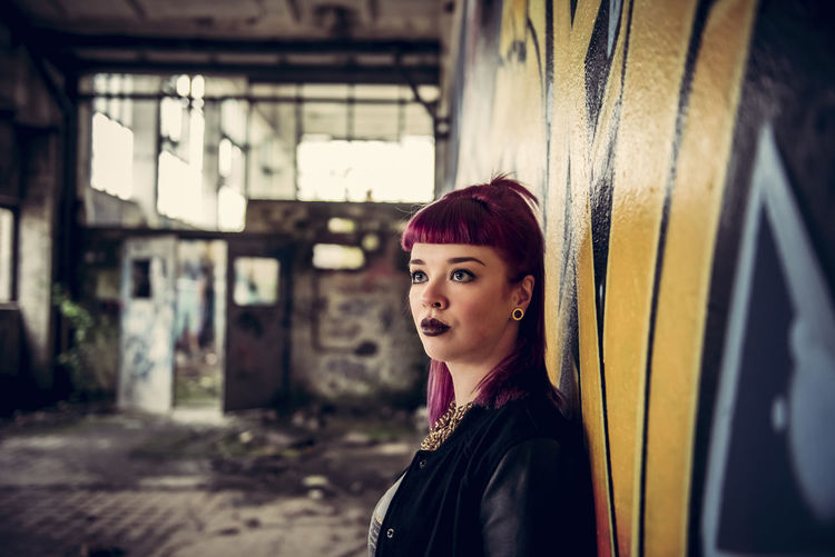 Young woman looking away standing against wall in abandoned building