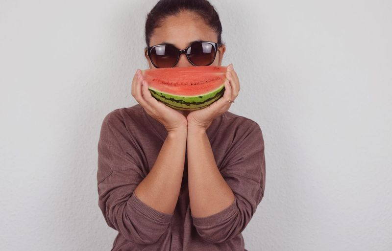 Portrait of woman wearing sunglasses holding melon against wall
