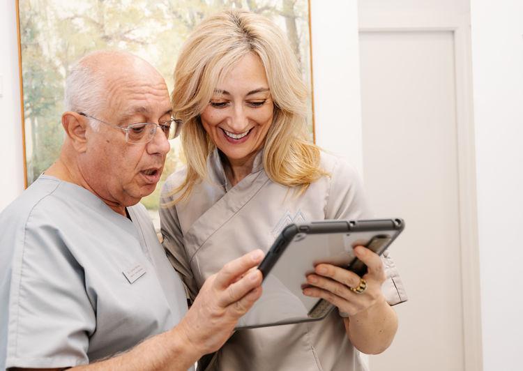 Couple holding smart phone while using laptop