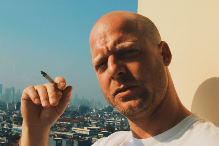 Close-up portrait of man smoking cigarette with cityscape in background