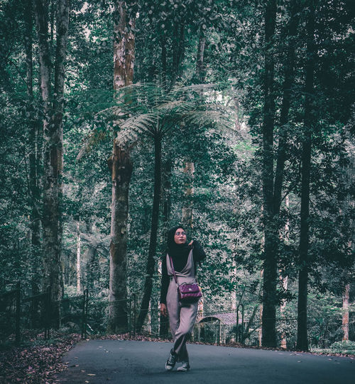 Full length of woman amidst trees in forest