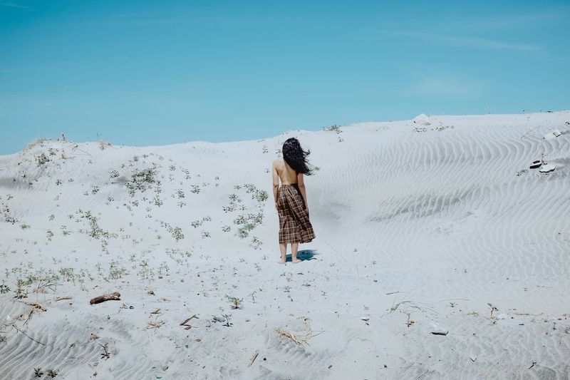 Rear view of woman walking on sand