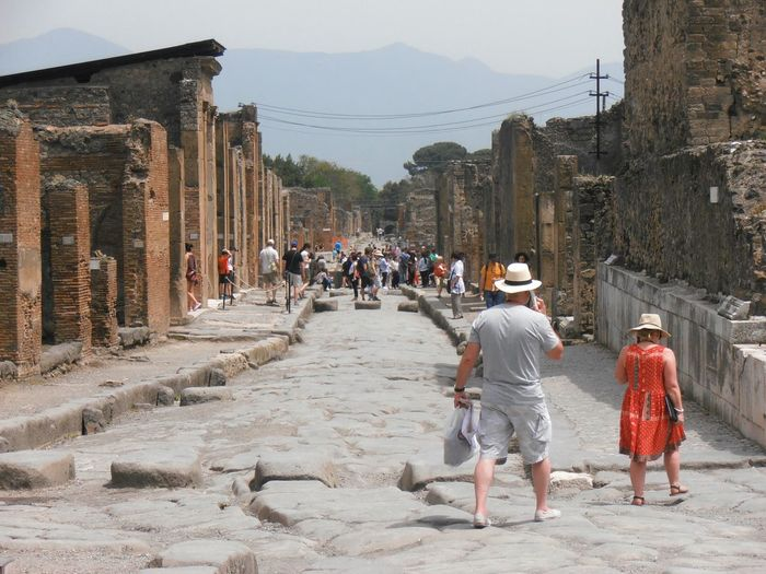 Group Of People Walking Along Ruined Structures