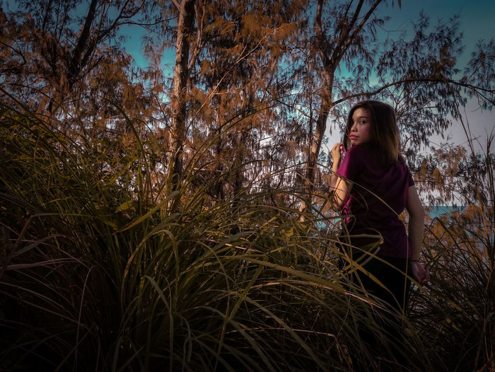 Portrait Of Woman Standing Amidst Dry Plants In Forest