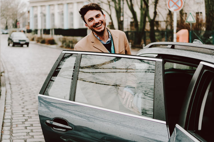 Portrait Of Smiling Young Man Entering In Car On Street