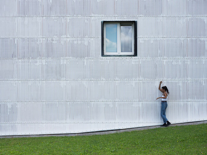 Side view of woman walking against wall