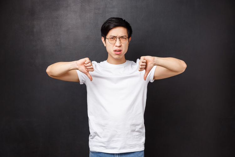 Man showing thumbs down gesture against black background