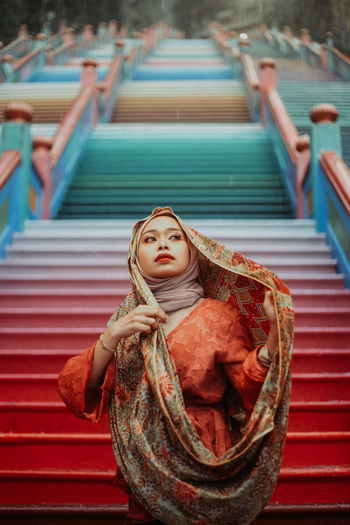 Beautiful woman wearing scarf while standing on steps