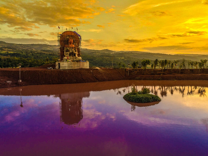 Reflection of temple in lake at sunset