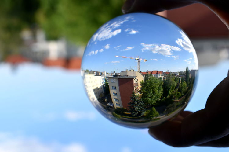 Close-up of hand holding crystal ball with reflection