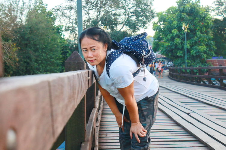 Portrait of woman with backpack standing by railing on footbridge
