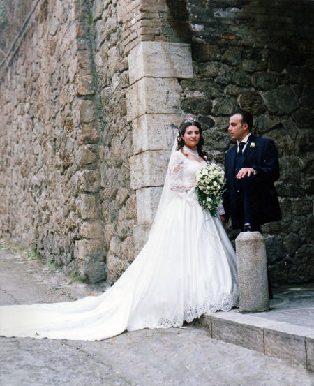 Portrait of bride with groom standing against wall