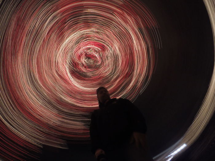 Low angle view of a man against abstract swirls