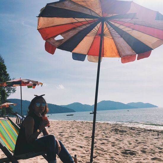 Woman sitting on beach against sky during sunny day