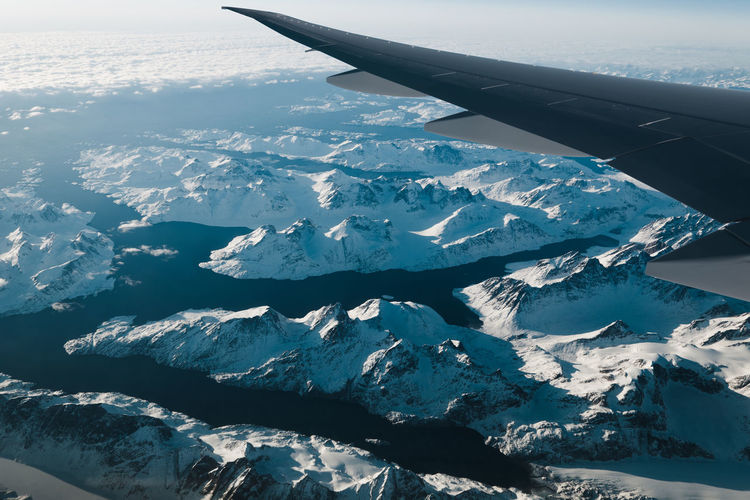 View of aircraft wing against snow covered landscape