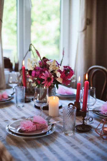 romantic summer dinner in cozy country house. Festive table setting with flowers and candles in purple tones Dinner Home Rustic Romantic Summer Table Setting Festive Table Candle Decoration Rural Life Countryside Farm Life Wooden Evening Kitchen Dining Table Guest Purple Elegant Wedding