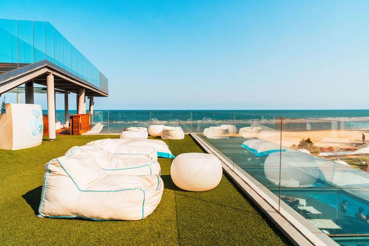 Lounge chairs by swimming pool at beach against clear sky