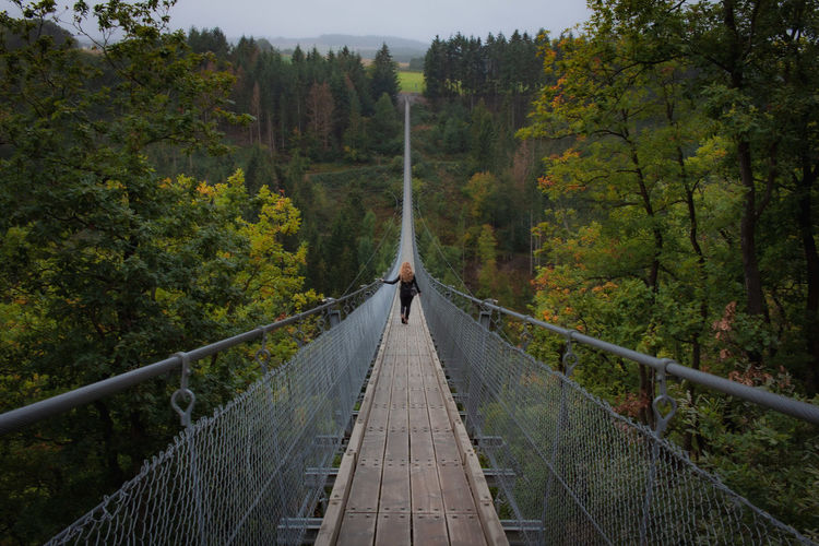 Woman on footbridge amidst trees in forest