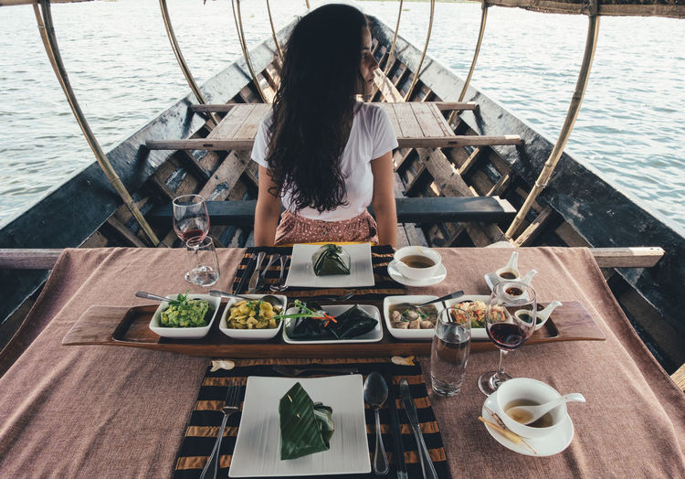 ASIA Lunch Travel Adult Boat Cultures Day Food And Drink Girl Hairstyle High Angle View Leisure Activity Lifestyles Mode Of Transportation Nature Nautical Vessel One Person Outdoors Real People Rear View Sea Sitting Transportation Water Women