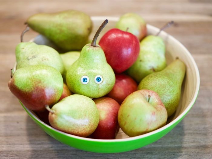 Close-up of pear with googly eyes in fruit bowl