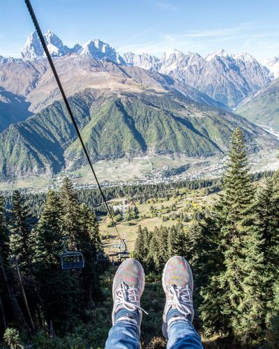 Human legs on cable railway above mountains