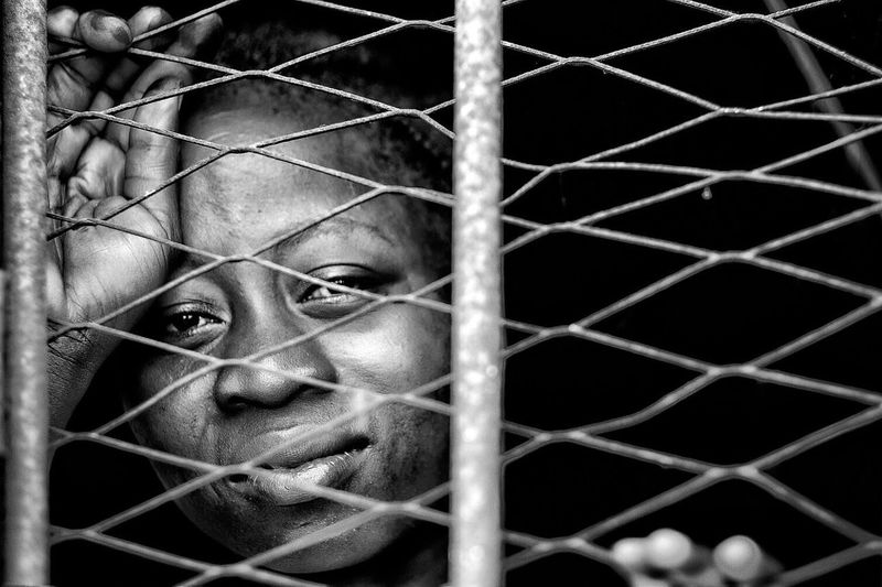 Portrait of young woman in cage seen through chainlink fence