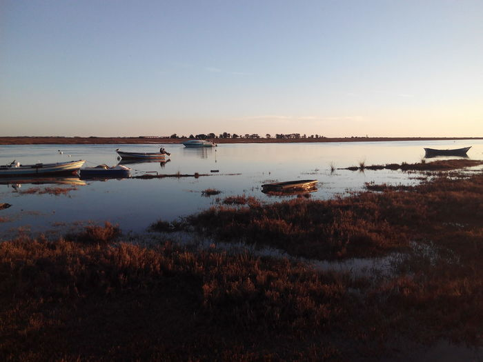 Boats Moored In Sea At Sunset