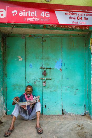Full length portrait of man sitting on door