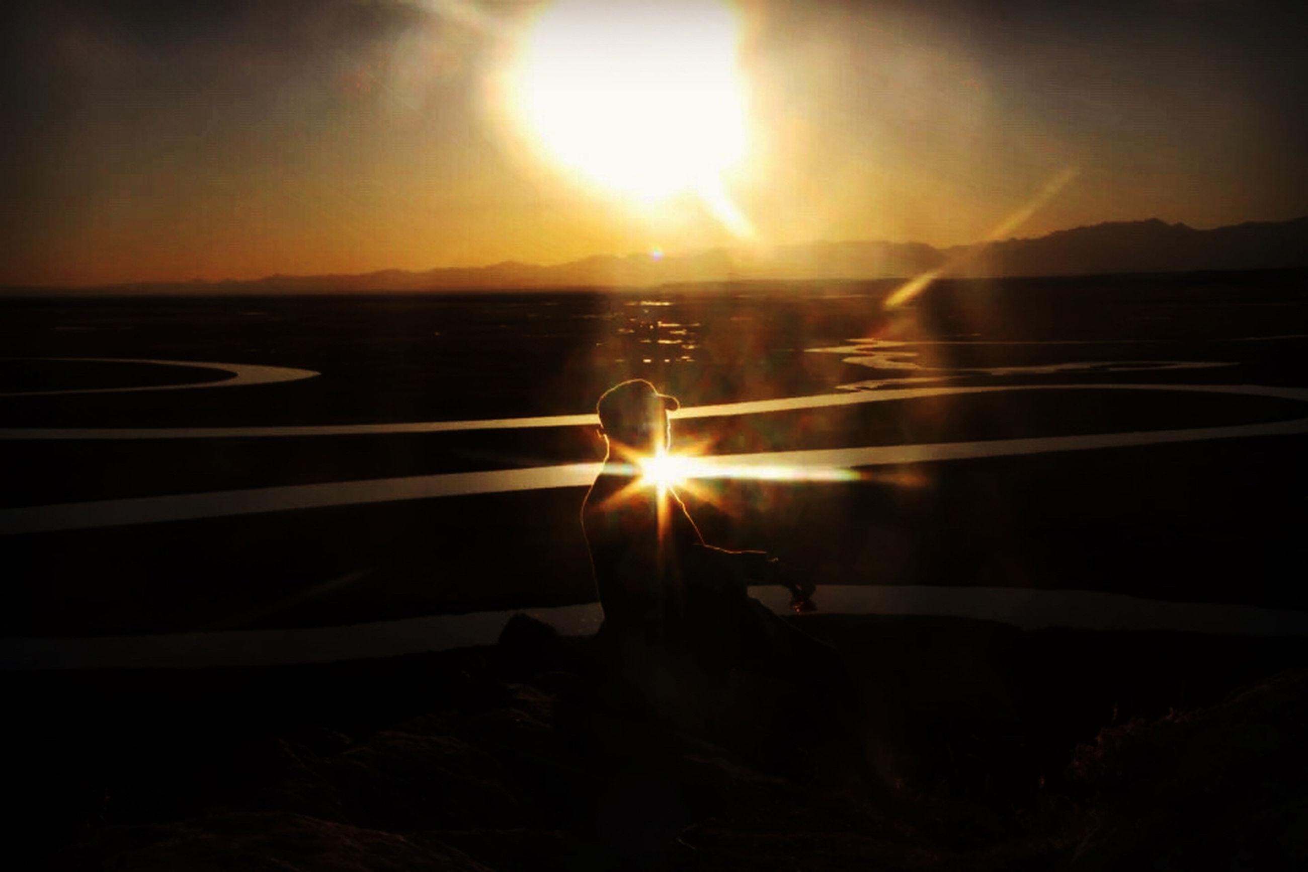 sun, sunset, sunbeam, silhouette, sunlight, mountain, tranquil scene, lens flare, scenics, tranquility, beauty in nature, water, nature, sky, idyllic, mountain range, reflection, orange color, sea, non-urban scene