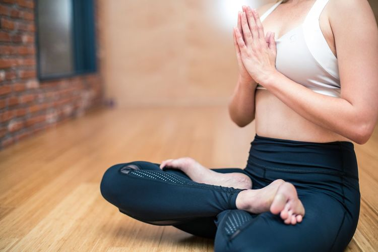Low Section Of Woman Practicing Yoga On Hardwood Floor