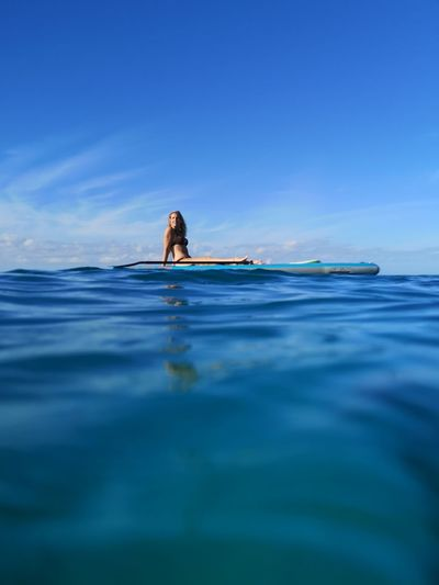 Surface level of woman sitting on paddle board in sea against sky