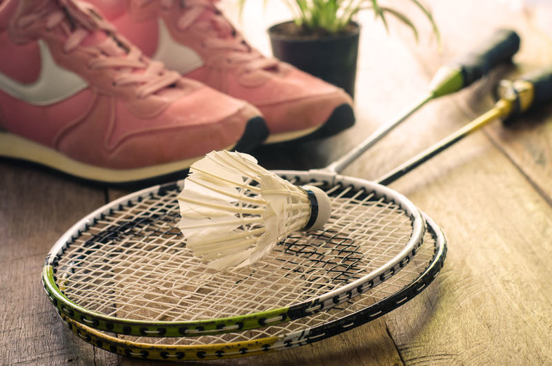 High angle view of rackets with shuttlecock and sports shoes on hardwood floor