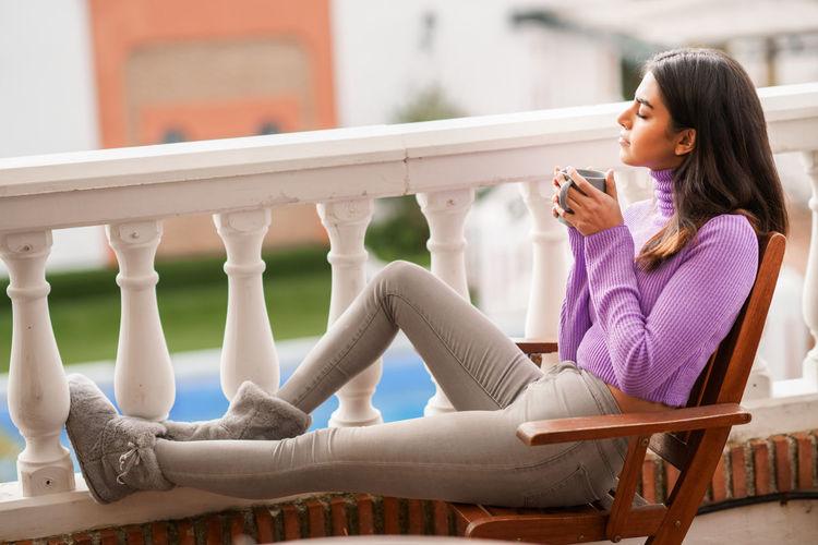 Woman enjoying coffee while relaxing in balcony