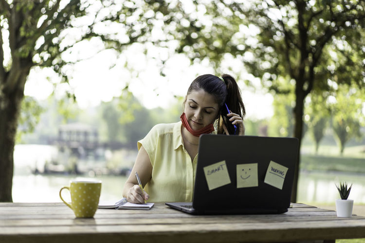 Smiling businesswoman wearing mask working at cafe