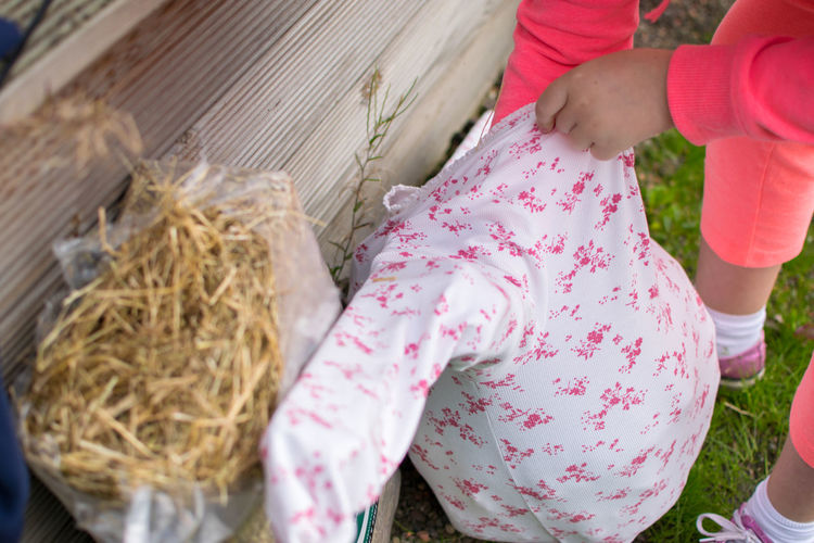 Low section of girl making scarecrow