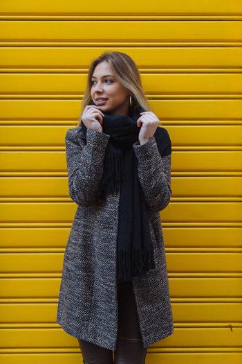 Woman standing against yellow shutter
