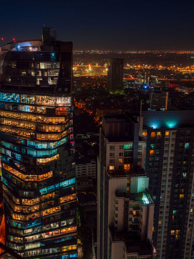 Bangkok highrise office building and apartment with light illumination at night time.