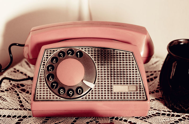Retro rotary dial phone sepia toned, household vintage telephone standing on table, old style antique communication domestic device in horizontal orientation, nobody. Accessory Antique Appliance Button Cable Call Contact Design Device Dial Dialing Handset No People Numbers Millennial Pink Old Old-fashioned Phone Retro Retro Styled Sepia Still Life Telephone Tinkle Vintage