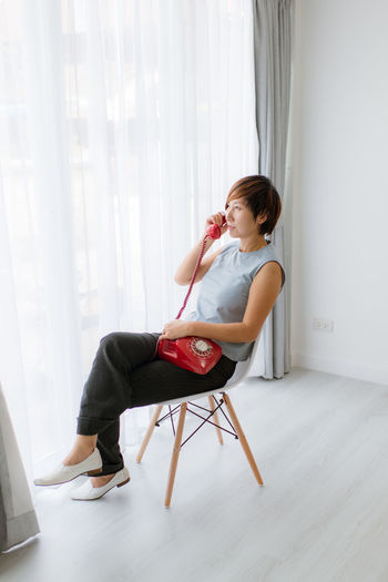 Woman using rotary phone while sitting on chair by window at home