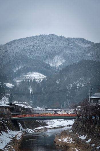 Bridge over mountain against sky during winter