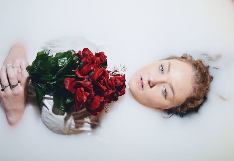Portrait of beautiful woman holding bouquet in bathtub