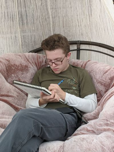Teenage boy drawing on a sketch pad while sitting in a large chair